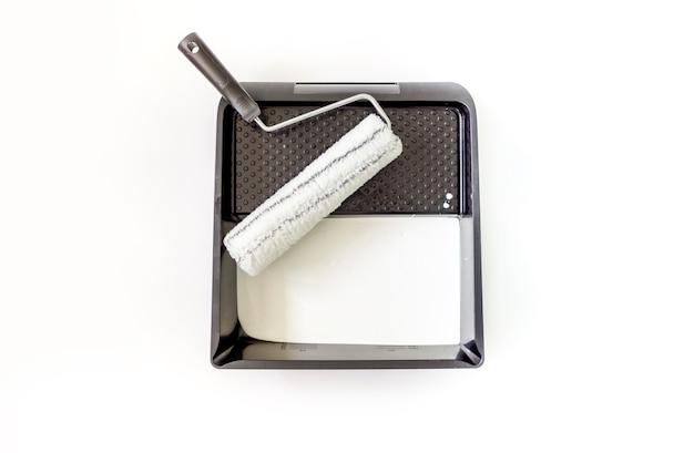 Roller met een verfbak en witte verf