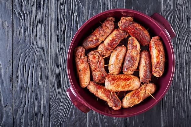 Rolletjes gestampte biefstuk gelaagd met parmaham, geraspte parmezaanse kaas en fijngehakte peterselie in een vuurpot, italiaanse keuken