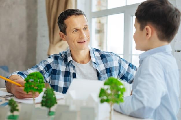 Rolmodel. vrolijke jonge architect vertelt zijn zoon over zijn nieuwe eco-city-project, toont modellen op tafel, terwijl de jongen vragen stelt tijdens het bezoek aan het kantoor van de vader