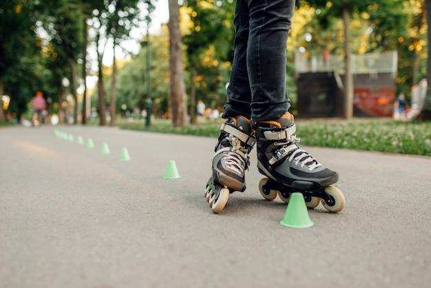 Rolschaatsen, mannelijke schaatser die rond de kegels in het park rolt. rolschaatsen in de stad, actieve extreme sporten buitenshuis, vrije tijd voor jongeren, rolschaatsen