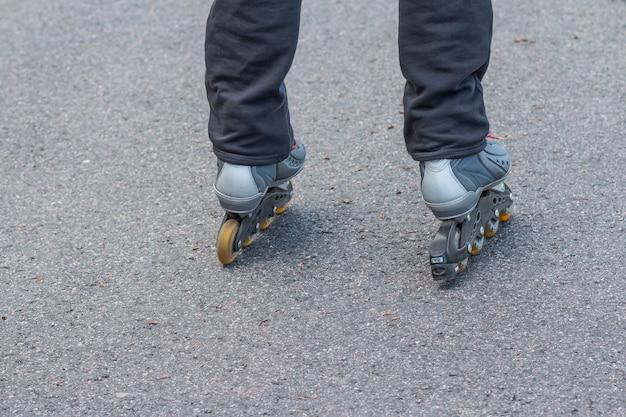 Rolschaatsen op straat in de stad, close-up van benen. benen van tieners rijden rolschaatsen in de straat. grijze rollen op de benen. benen van sport mannen op een rolschaatsen lopen close-up