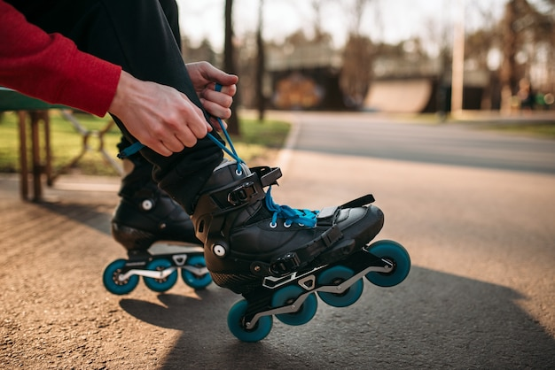 Rolschaatser zittend op een bankje en rijgen schaatsen