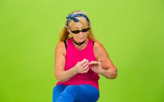 Rolschaatster. senior vrouw in ultra trendy kleding geïsoleerd op heldergroen