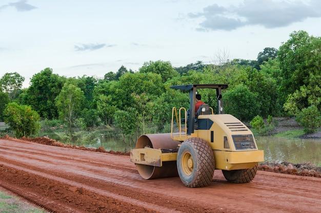 Rolstoomwals of trillende rolmachine die aan wegenbouwplaats van nieuwe weg werken.