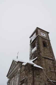 Romaanse kerktoren met een met sneeuw bedekte klok