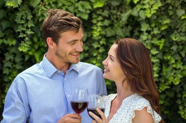 Romanic paar dat elkaar bekijkt terwijl het houden van wijnglazen