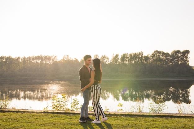 Romantica, natuur en mensen concept - jong koppel kussen op het strand van het meer en knuffelen
