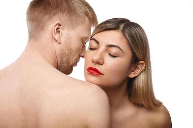 Romantiek en passie concept. foto van aantrekkelijk volwassen kaukasisch paar knuffelen: mooie vrouw met rode lippenstift en neusring ogen sluiten, de goede lichaamsgeur van haar bebaarde man inademen