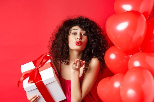 Romantiek en valentijnsdag concept. vrij krullend-haired meisje in een rode jurk die haar liefde verzendt, luchtkus blaast op camera, geschenk van minnaar houdt, staande in de buurt van harten op rode achtergrond.