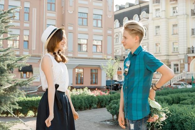 Romantiek in een paar tieners, tienerjongen verrassingen geeft boeket bloemen