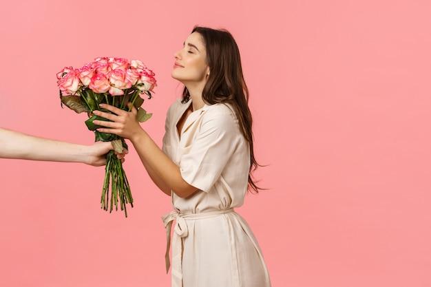 Romantiek, valentijnsdag en geluk concept. schitterende jonge vrouw die levering ontvangt, die mooie rozen ruikt als hand die boeket uitrekken aan meisje, blij glimlachen, kreeg verrassingsgift