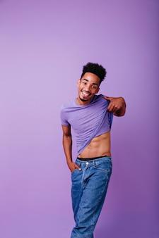 Romantisch afrikaans model dat zijn t-shirt opstijgt. indoor foto van lachende schattige zwarte man.