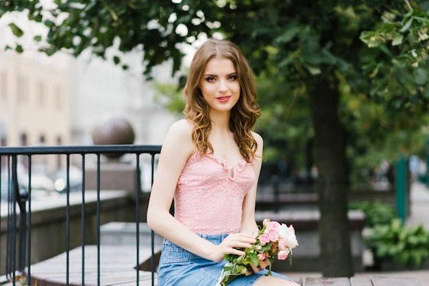 Romantisch beeld van een jong meisje dat op een de zomerstraat loopt in het park