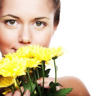 Romantisch beeld van een jonge vrouw met gele chrysanten