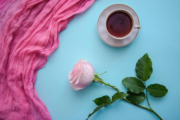 Romantisch beeld van thee, roos en roze stof op een blauwe achtergrond