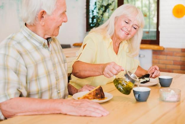 Romantisch bejaard paar dat thee in koffie heeft