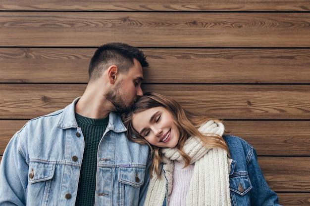 Romantisch blond meisje liggend op de schouder van vriendje met gesloten ogen. indoor portret van europese brunette man kussen vriendin haar op houten muur.