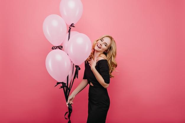 Romantisch blond vrouwelijk model viert verjaardag met een charmante glimlach. bevallig krullend meisje met ballonnen vakantie-evenement voorbereiden.