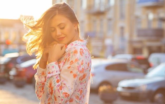Romantisch brunette meisje met gesloten ogen die zich voordeed op de achtergrond van de wazige stad met zonnestralen. ruimte voor tekst