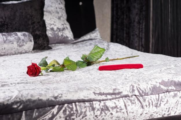 Romantisch cadeau en enkele rode roos met lange steel in een slaapkamer die de liefde symboliseert voor het vieren van een jubileum of valentijnsdag met een geliefde loved