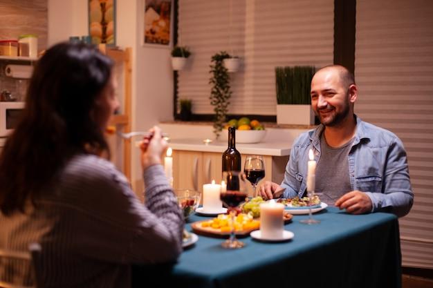 Romantisch diner met een man op de voorgrond die zich gelukkig voelt met zijn vrouw in de eetkamer. ontspan gelukkige mensen die rammelen, aan tafel zitten in de keuken, genieten van de maaltijd, jubileum vieren.