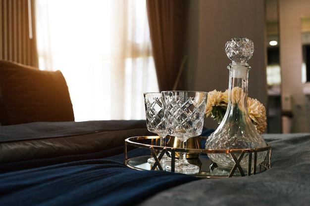 Romantisch diner met fles en glas vloeistof op bed voorbereiden