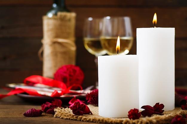 Romantisch diner met kaarsen, wijn en bloemblaadjes