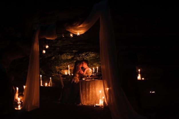 Romantisch diner van een jong stel bij kaarslicht in de bergen