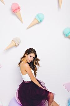 Romantisch donkerbruin meisje in violet lange rok speels op zoek, rustend in kamer met lief interieur. portret van charmante krullende jonge vrouw die zich voordeed op muur versierd met dessert spullen.