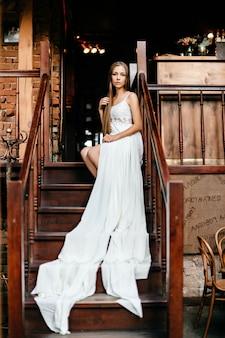 Romantisch doordachte meisje in lange witte jurk zittend op de trap