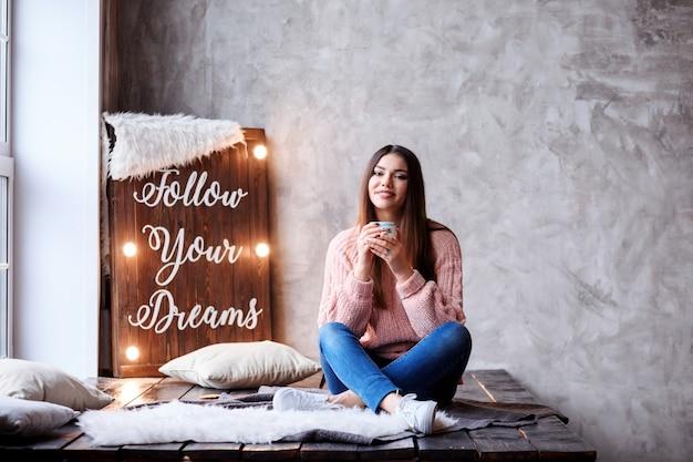 Romantisch dromend wit meisje in gezellige sweater met kopje thee in haar handen voor het lichtpaneel met belettering follow your dreams. mooi modern interieur. mensen motiveren.