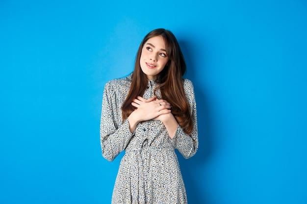 Romantisch dromerig meisje in jurk kijkend naar de linkerbovenhoek, hand in hand op het hart en dagdromen, iets leuks voorstellend, staande op blauw.
