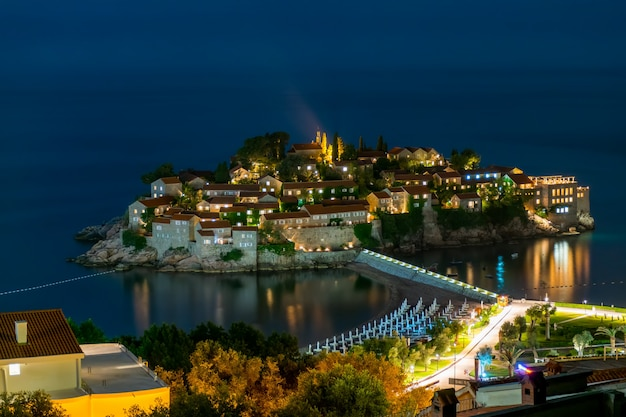 Romantisch eiland sveti stefan gloeit in de nacht met het maanlicht