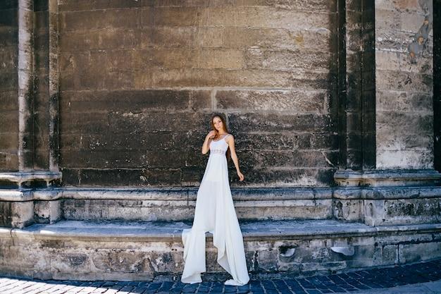 Romantisch elegant meisje in lange witte jurk poseren over oude stenen muur