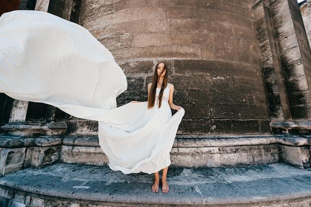Romantisch elegant meisje in lange witte zwierige jurk poseren over oude stenen muur