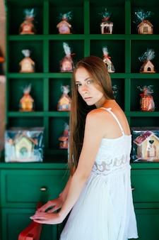 Romantisch elegant meisje in witte jurk poseren over versierde muur
