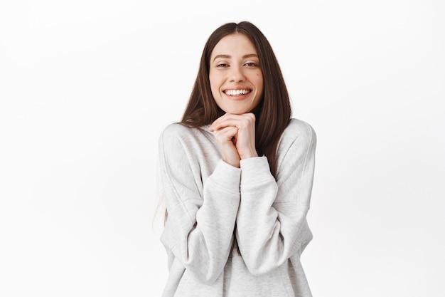 Romantisch en schattig meisje dat met bewondering en sympathie kijkt, iets bewondert, naar een mooie, mooie scène kijkt, het hoofd op de handen laat rusten en glimlacht, over een witte muur staat