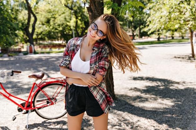 Romantisch europees meisje dat na fietstocht geniet. buiten foto van lachende mooie vrouw in park met fiets.