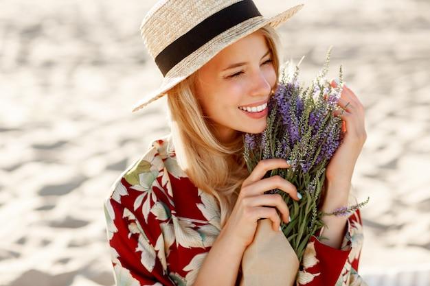 Romantisch gelukkig close-up portret van charmante blonde meisje in strooien hoed ruikt bloemen op het strand van de avond, warme zonsondergang kleuren. boeket van lavendel.