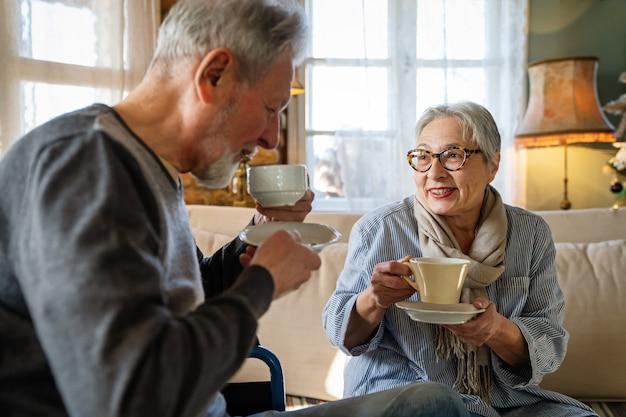 Romantisch gelukkig senior paar verliefd thuis. volwassen man met handicap in rolstoel die plezier heeft met vrouw