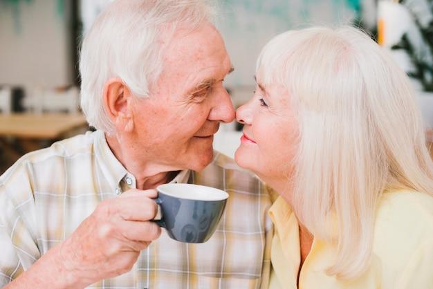 Romantisch glimlachend rijp paar dat met neuzen raakt