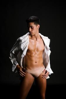 Romantisch half geklede mannelijke houding met handen op de heupen