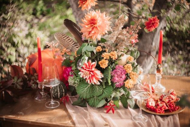 Romantisch herfstdecor: een boeket dahlia's, granaatappels, kaarsen, pompoenen en glazen