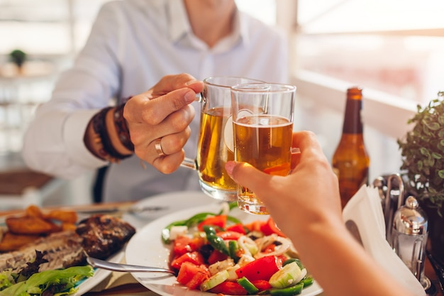 Romantisch huwelijksreisdiner voor twee. paar toast en drinkt alcohol. mensen eten griekse salade en zeevruchten in café