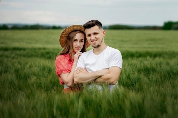 Romantisch jong gelukkig stel in een gerstveld. meisje in een rode jurk en een jongen. portret van paar wandelen in het gras.
