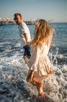 Romantisch jong koppel verliefd samen op het zand wandelingen langs het strand van de middellandse zee. zomervakantie in een warm land.