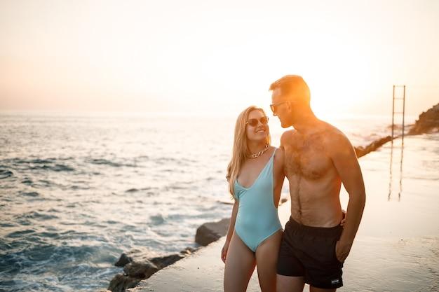 Romantisch jong koppel verliefd samen wandelen bij zonsondergang langs het strand van de middellandse zee. zomervakantie in een warm land. gelukkig getrouwd stel op vakantie in turkije. selectieve focus