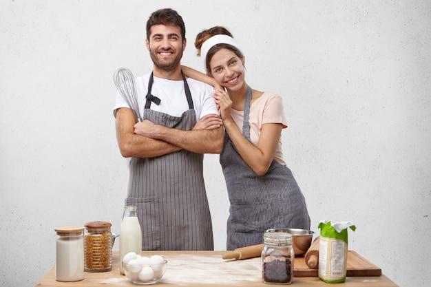 Romantisch jong paar dat italiaans voedsel thuis voorbereidt. foto van charmante dame met hoofdband die zich in keukentafel bevindt