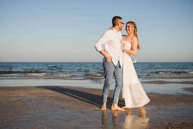 Romantisch jong paar die elkaar bekijken die zich dichtbij het overzees bij strand bevinden