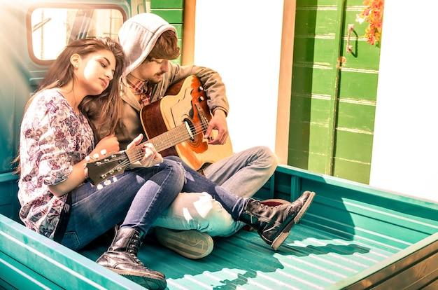 Romantisch jong paar liefhebbers gitaar spelen buiten met sunshines na de regen